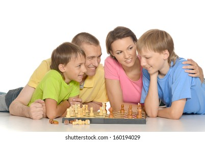 Family of four playing chess lying on the floor