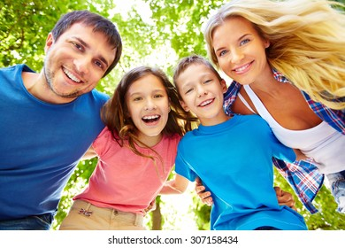 Family of four posing with happy faces