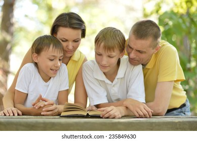 Family of four reading outdoors at table with book
