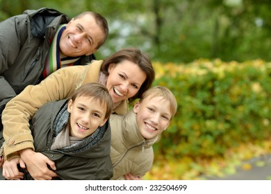 family of four relaxing in the park in autumn