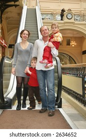 family of four in shop and escalator