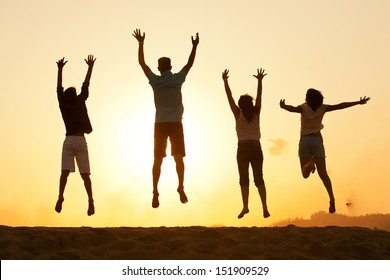 Family of four silhouette by a sunset jumping for joy