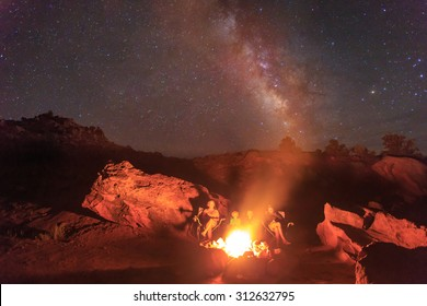 Family of four sitting by a campfire in the Utah desert with the milky way and stars in the sky above, USA.