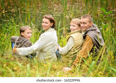 Family of four sitting at lake in autumn forest