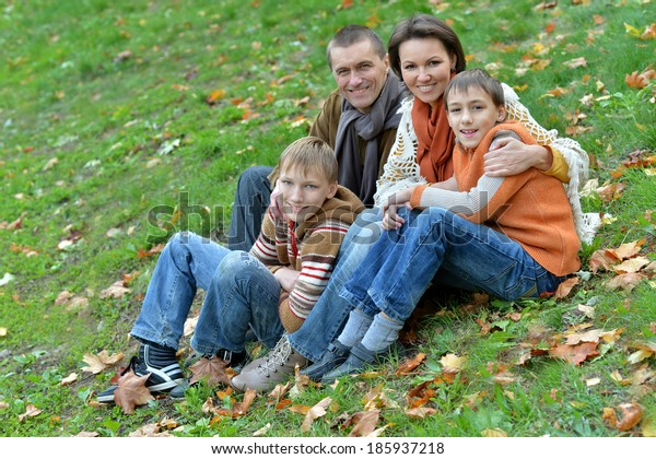 Family of four sitting on a grass in autumn park
