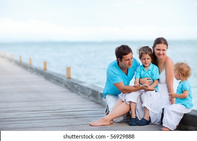 Family of four sitting on wooden jetty by the ocean