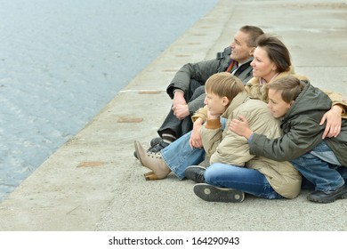 Family of four sitting at river embankment in autumn