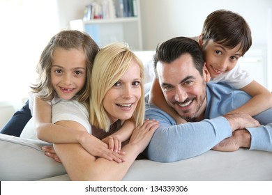 Family of four sitting in sofa at home