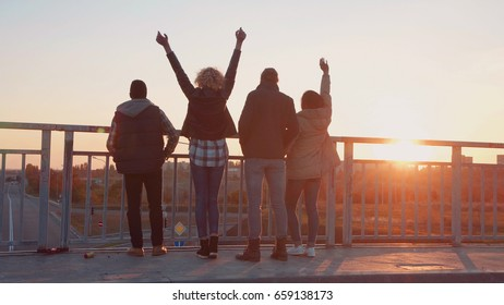 Family of four stands at barrier on bridge in city to observe nature as the sun sets beyond the tree line