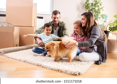 Family of four with their pet dog on the rug of the new apartment having fun