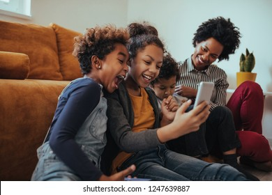 Family of four using modern technology at home