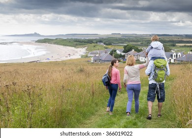 A family of four are walking along the sand dunes. The little boy is getting carried on his fathers shoulders.