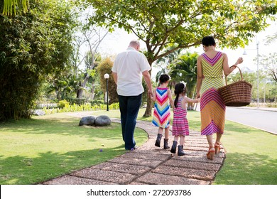 Family of four walking in park, view from the back