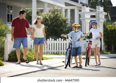 Family of four walking together on sidewalk with bicycles.