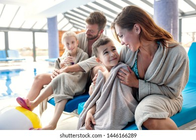 Family of four warming up under the towels after being in the swimming pool, family concept