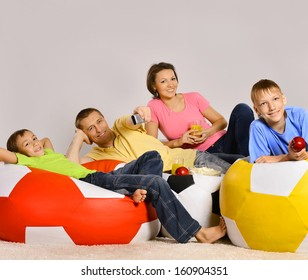 Family of four watching tv sitting on colored cushions