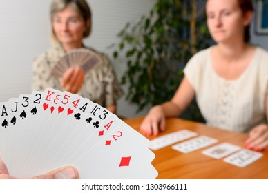 Family foursome playing Contract Bridge at home