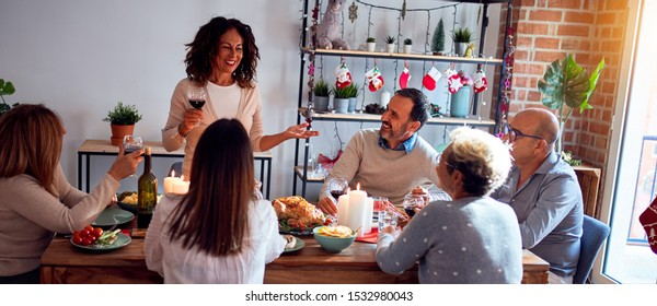 Family and friends dining at home celebrating christmas eve with traditional food and decoration, making a toast for new year best wishes