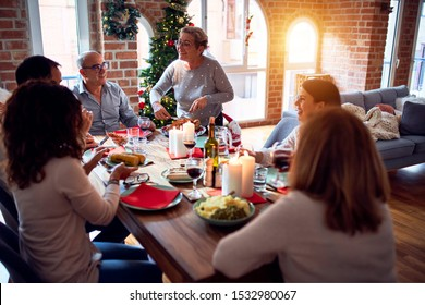 Family and friends dining at home celebrating christmas eve with traditional food and decoration, preparing turkey for dinner