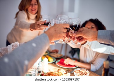Family and friends dining at home celebrating christmas eve with traditional food and decoration, making a toast with best wishes with glass of wine