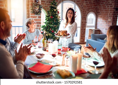 Family and friends dining at home celebrating christmas eve with traditional food and decoration, showing proud turkey cooking