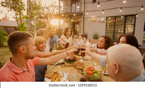 Family and Friends Gathered Together at the Table Raise Glasses and Bottles To Make a Toast and Clink Glasses. Big Family Garden Party Celebration.