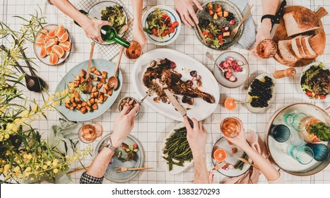 Family or friends gathering dinner. Flat-lay of hands of people eating roasted lamb shoulder, salads, vegetables, drinking rose wine over white checkered tablecloth, top view. Celebration party dinner