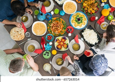 Family and friends gathering together at home for eating dinner