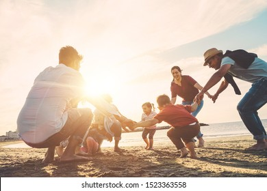 Family friends having fun on the beach at sunset - Fathers, mothers, children and uncles playing together - Focus on bodies - Love, party and celebrating concept - Soft focus on right man face