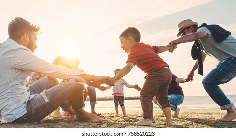 Family friends having fun on the beach at sunset - Fathers, mothers, children and uncles playing together - Focus on bodies - Love, relationship, party and celebrating concept - Soft focus on boy