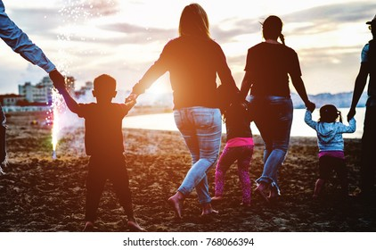 Family friends holding eache others hands around fireworks at sunset on the beach - Adult people having fun with their children for holidays outdoor - Focus on boy silhouette - Love and fest concept
