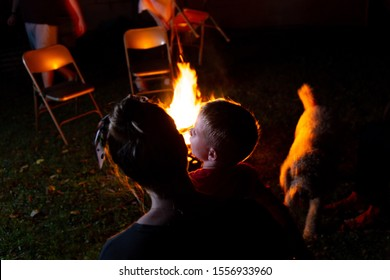 Family and Friends Sit Around a Backyard Fire Pit and Toast Smores