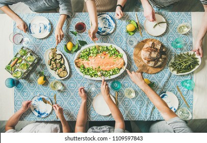 Family or friends summer party or seafood dinner. Flat-lay of group of mutinational people with different skin color at big table eating delicious food together. Summer gathering or celebration