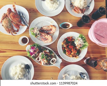 Family or friends in summer party or seafood set dinner. Flat-lay of group of mutinational people at big table eating delicious food together. Summer gathering or celebration. top view background.