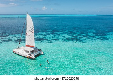 Family and friends swimming near a beautiful catamaran in the paradise turquoise lagoon of the east coast of Mauritius