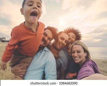 Family friends taking selfie on the beach at sunset - Fathers, mothers, children and uncles having fun together - Love, relationship, tech and party concept - Soft focus on right woman face