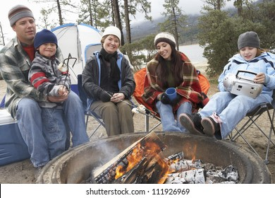 Family in front of campfire ready to toast marshmallow