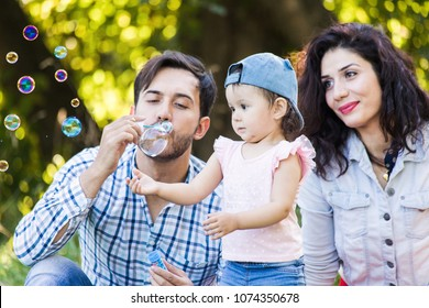 Family fun in nature. Happy mom, dad and daughter blow bubbles in the park.