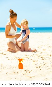 Family fun on white sand. Closeup on spf bottle on the seacoast and mother and daughter in swimwear in background