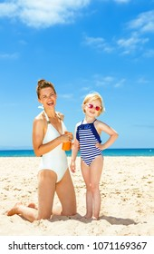 Family fun on white sand. happy young mother and daughter in swimsuit on the seacoast applying sun block