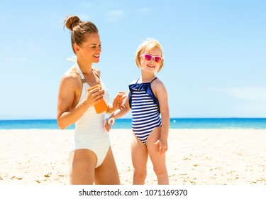 Family fun on white sand. happy young mother and child in beachwear on the seacoast applying sun block