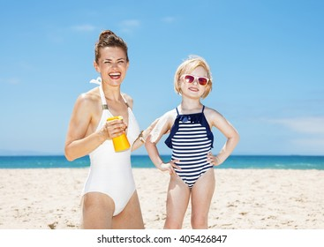 Family fun on white sand. Smiling mother applying sunscreen on daughter's arm at sandy beach on a sunny day