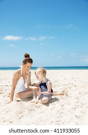 Family fun on white sand. Smiling mother and girl in swimsuits at beach on a sunny day playing