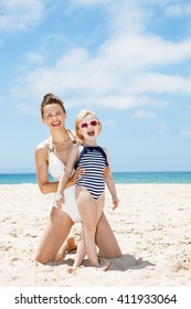 Family fun on white sand. Smiling mother and child in swimsuits at sandy beach on a sunny day
