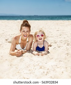 Family fun on white sand. Happy mother and child in swimsuits laying on sandy beach on a sunny day