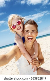 Family fun on white sand. Smiling mother and daughter in swimsuits taking selfies at sandy beach on a sunny day