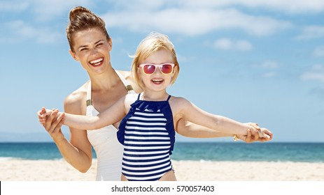 Family fun on white sand. Smiling mother and child in swimsuits playing at sandy beach on a sunny day