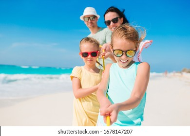 Family fun. Parents with kids on the beach