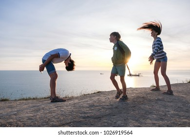 Family fun pastime on a mountain with seaside view. Dad, mom, and son dance at sunset. Side view.