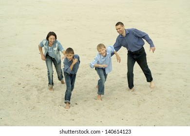 Family fun running barefoot in the sand